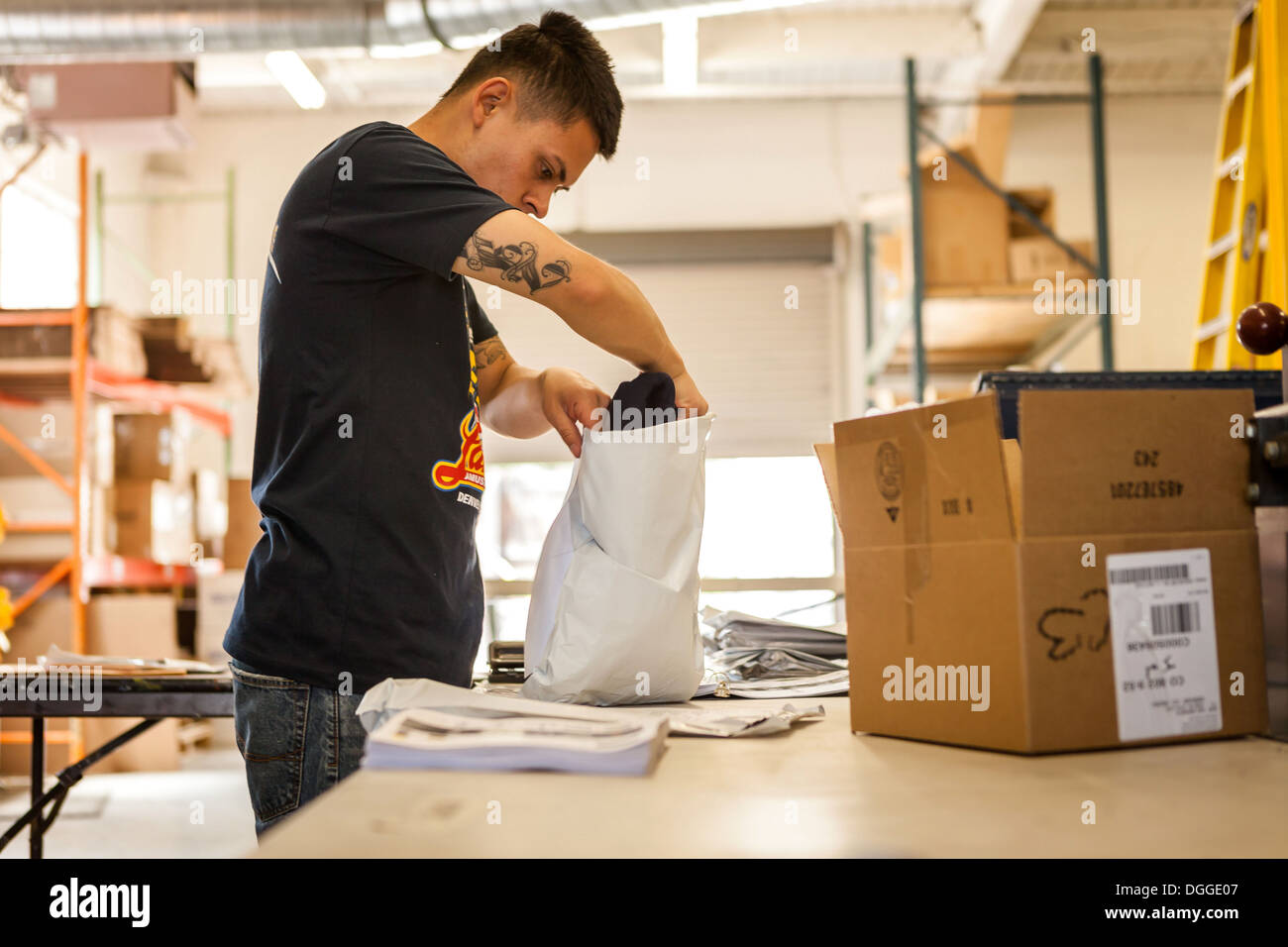 Worker packing garment in screen print workshop - Stock Image