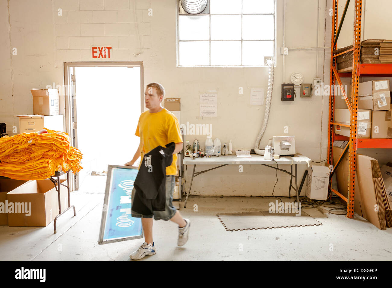 Worker carrying frame and t-shirt in screen printing workshop - Stock Image