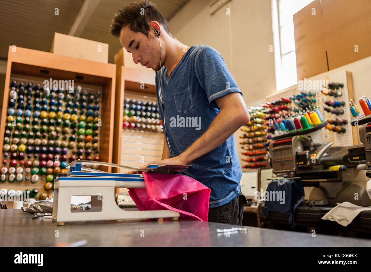 Worker using embroidery machine in t-shirt printing workshop - Stock Image