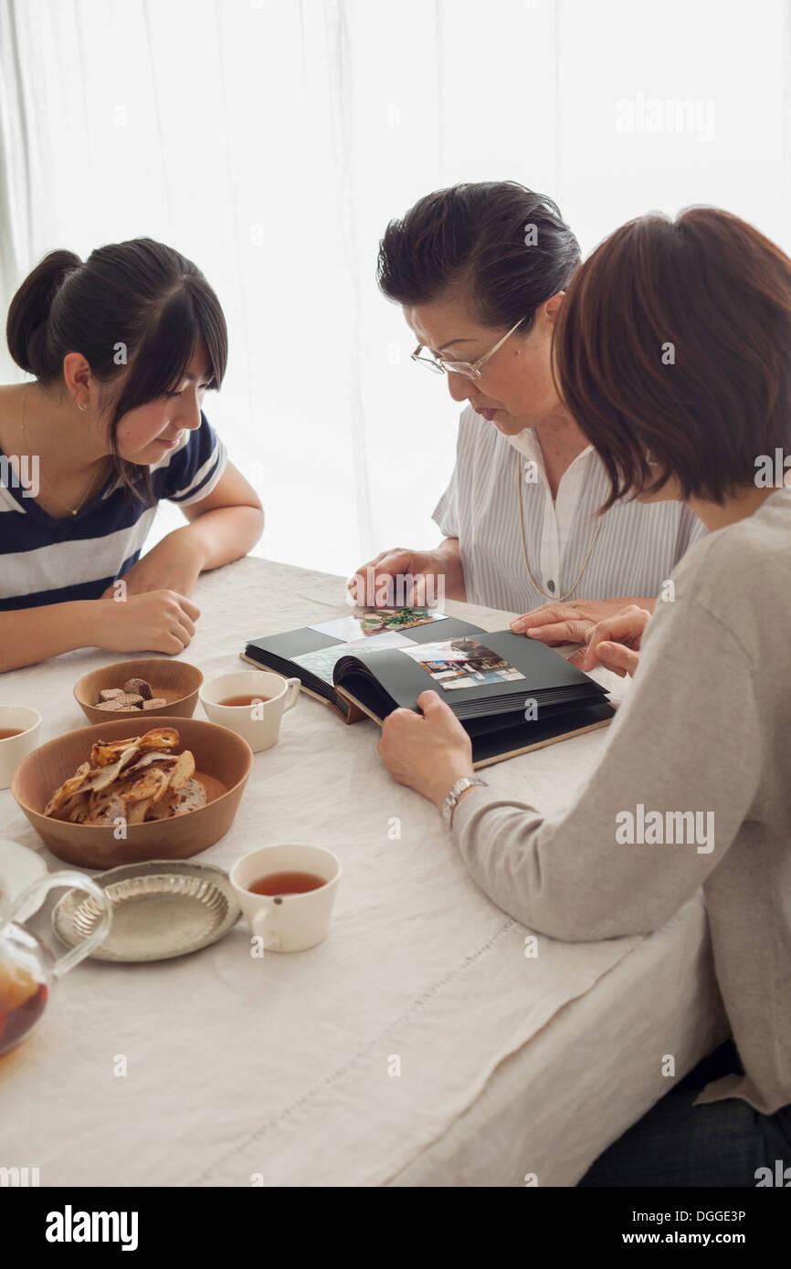 Three generation family looking at photograph album - Stock Image