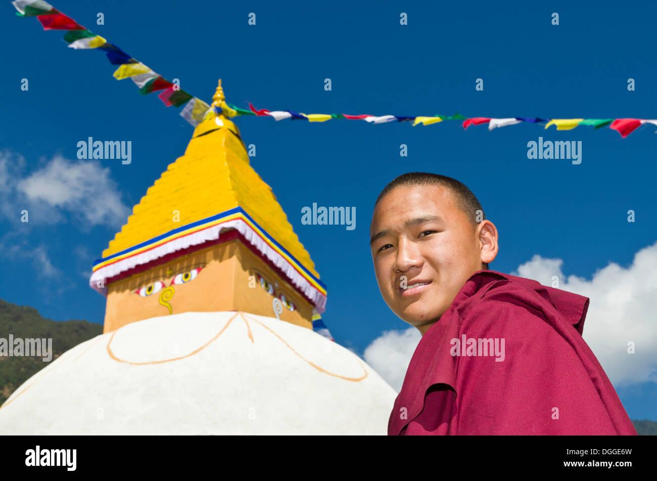 Portrait of a young tibetean monk, white stupa with prayerflags in the back, Bhandar, Solukhumbu District, Sagarmāthā Zone - Stock Image
