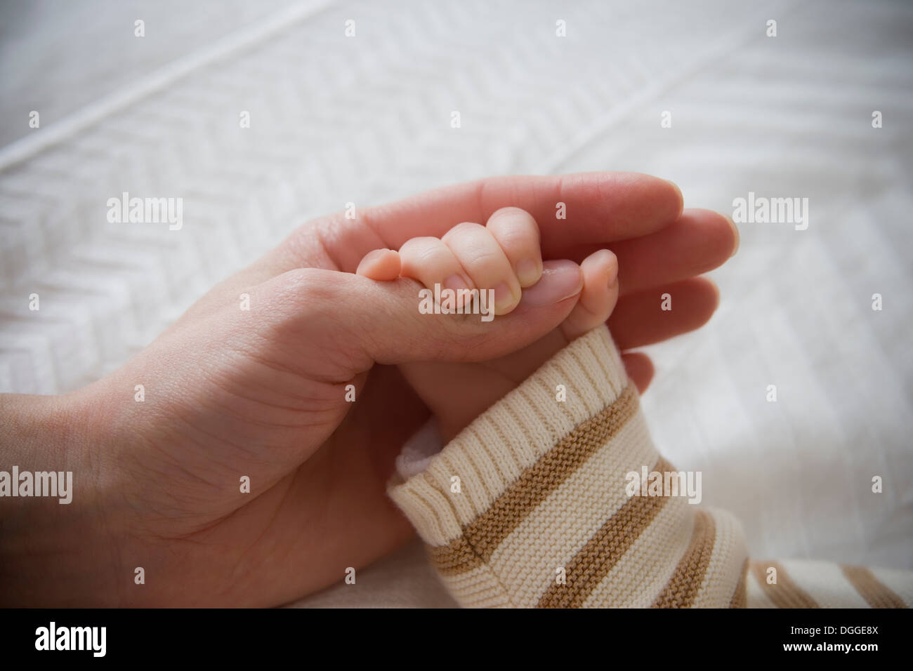 Baby boy holding mother's hand, close up - Stock Image