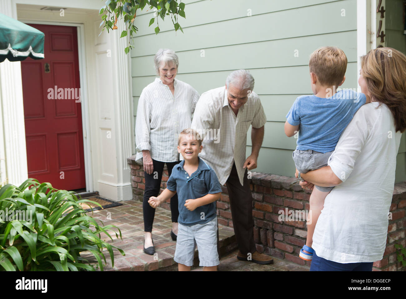 Senior couple greeting family at home - Stock Image