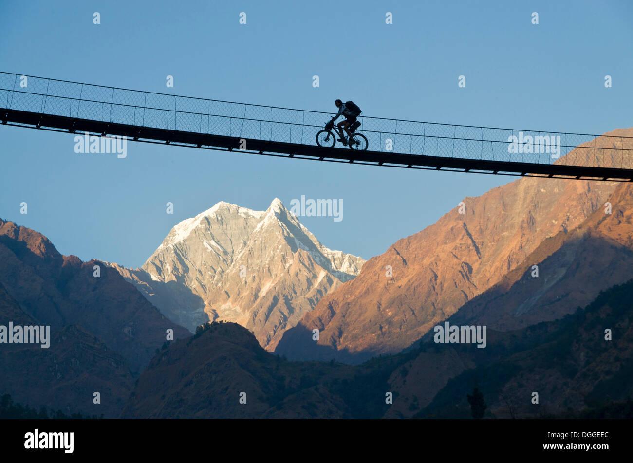 Cyclist crossing a suspension Bridge over Kali Ghandaki Valley, Nilgiri Mountain in the back, Tatopani, Annapurna Region, Nepal - Stock Image