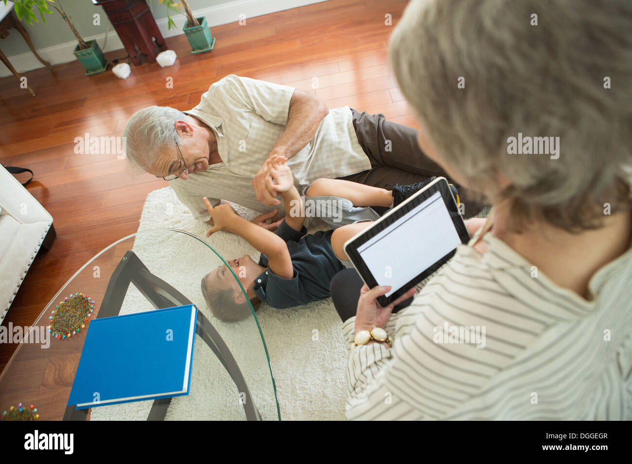Senior man tickling grandson on rug - Stock Image