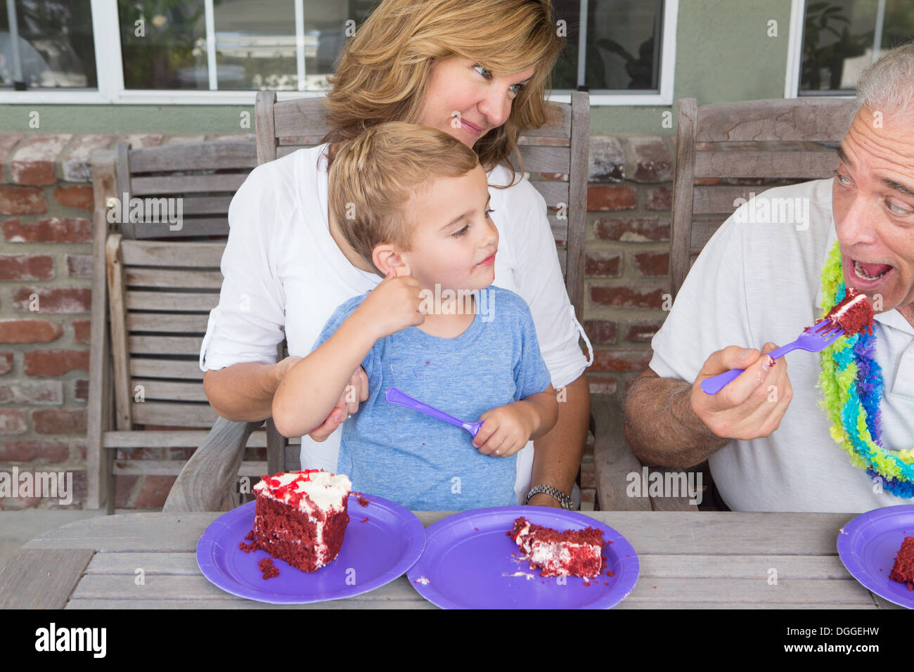 Grandson and mother watching senior man eat birthday cake - Stock Image