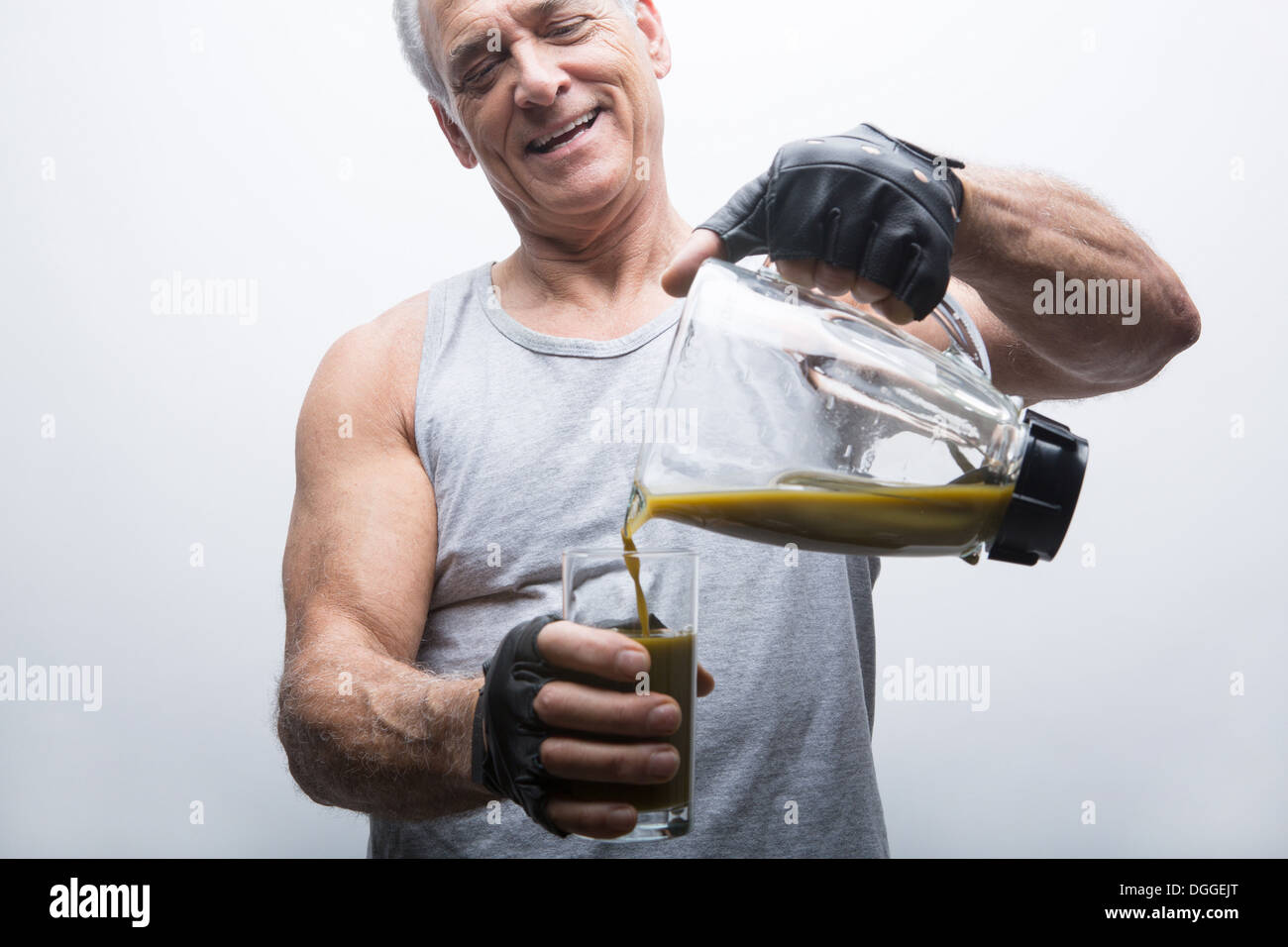Senior man pouring smoothie from blender into glass - Stock Image