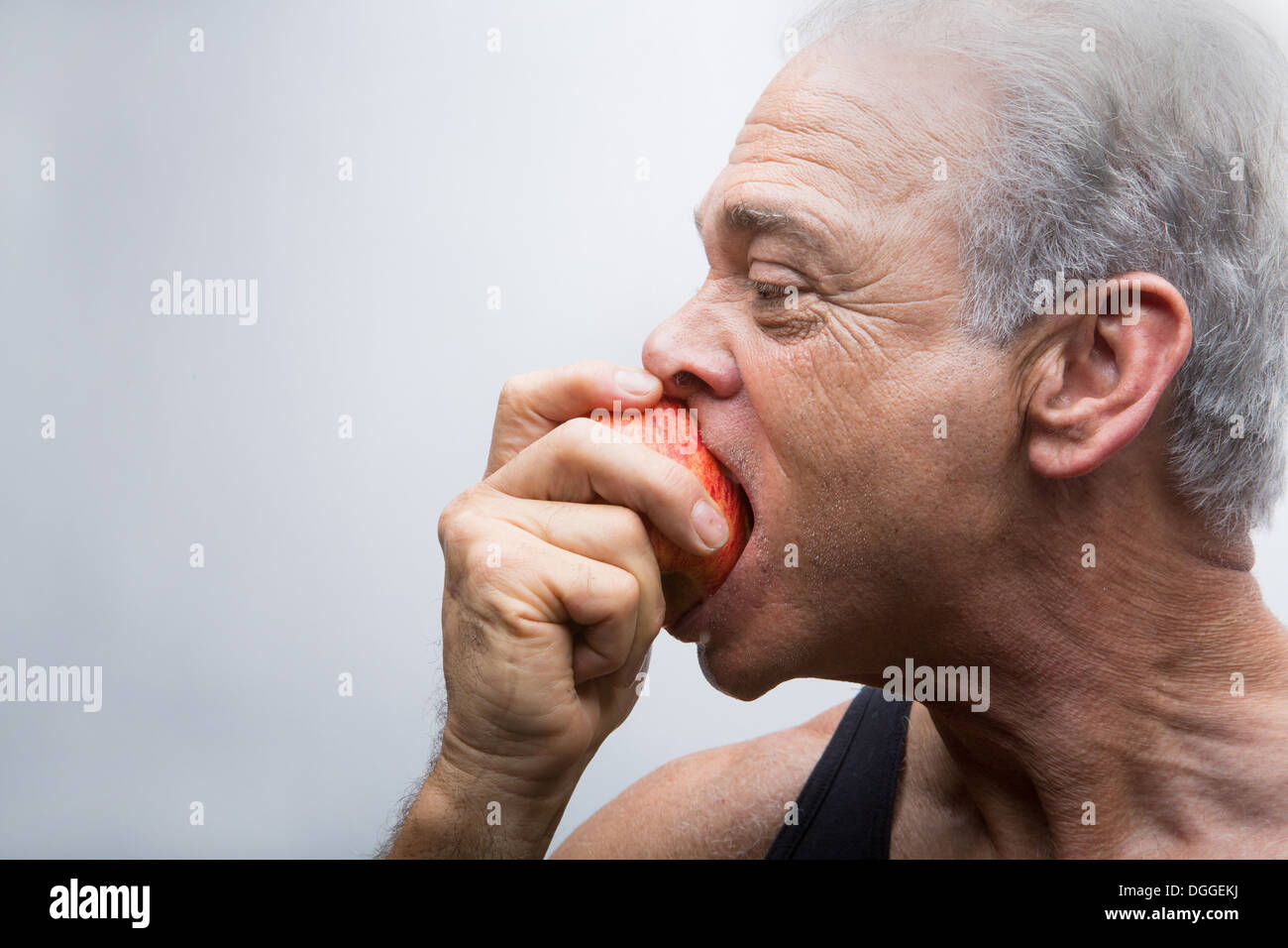 Senior man eating apple, close up - Stock Image