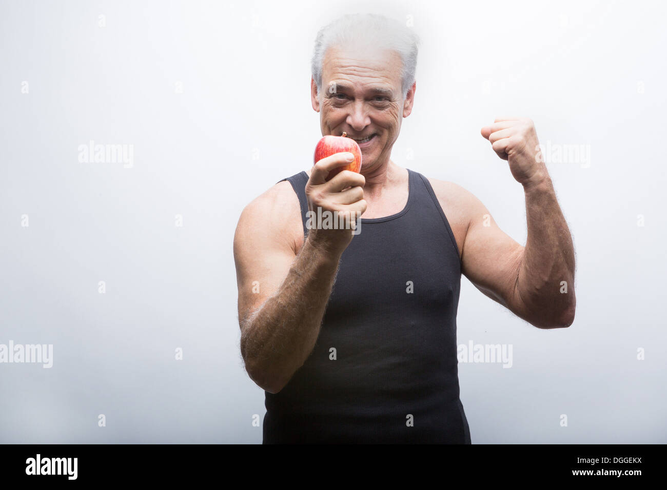 Senior man flexing muscle and holding apple, smiling - Stock Image