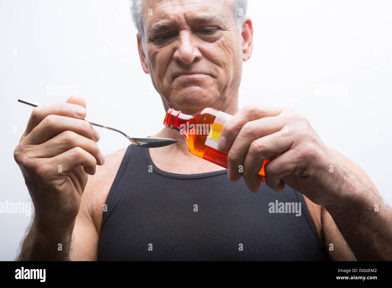 Senior man pouring medicine from bottle - Stock Image