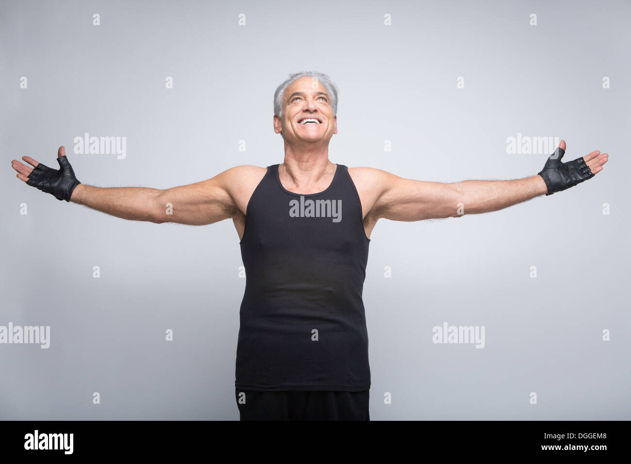 Senior man with arms out looking up - Stock Image