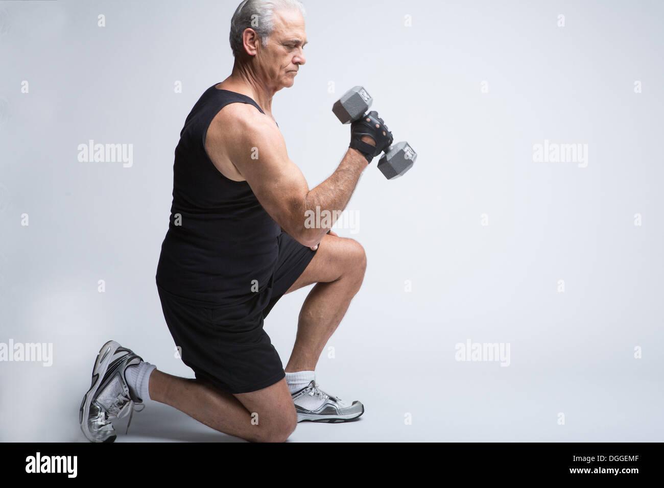 Senior man in sports clothing lifting broccoli - Stock Image