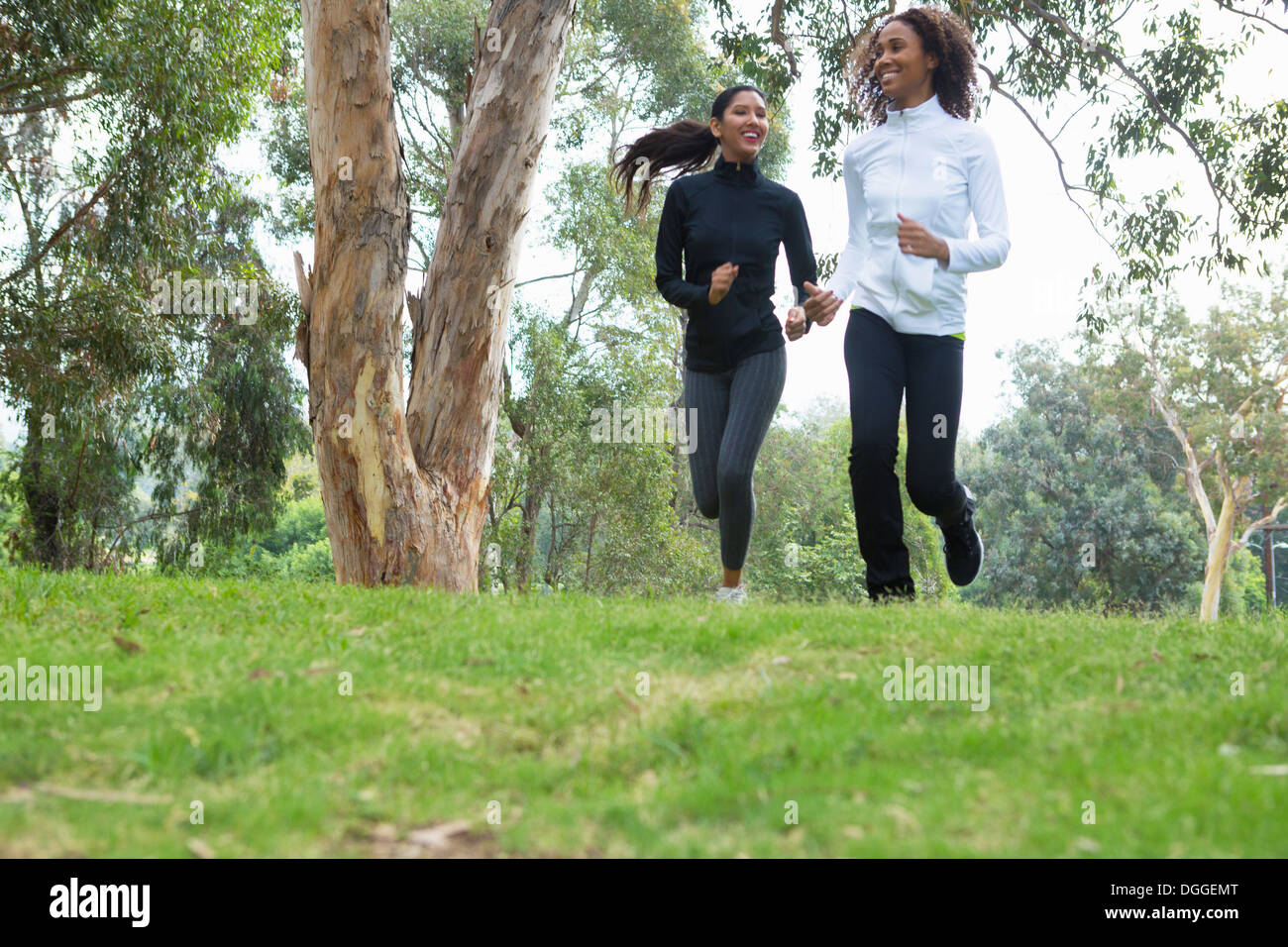 Young and mid adult woman jogging together - Stock Image