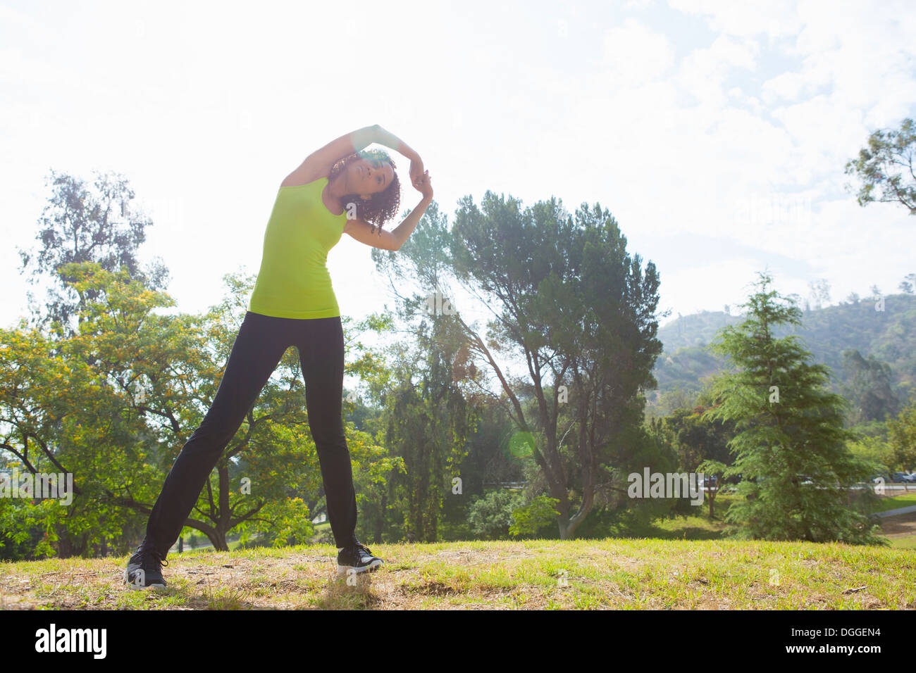 Mid adult woman stretching in park - Stock Image