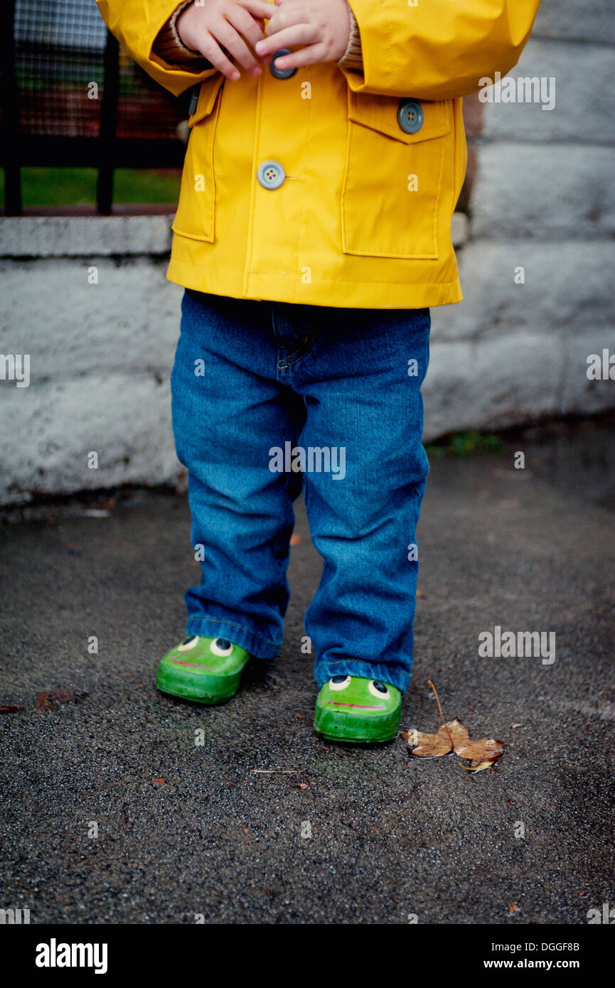 Close up of female toddler wearing yellow raincoat Stock Photo