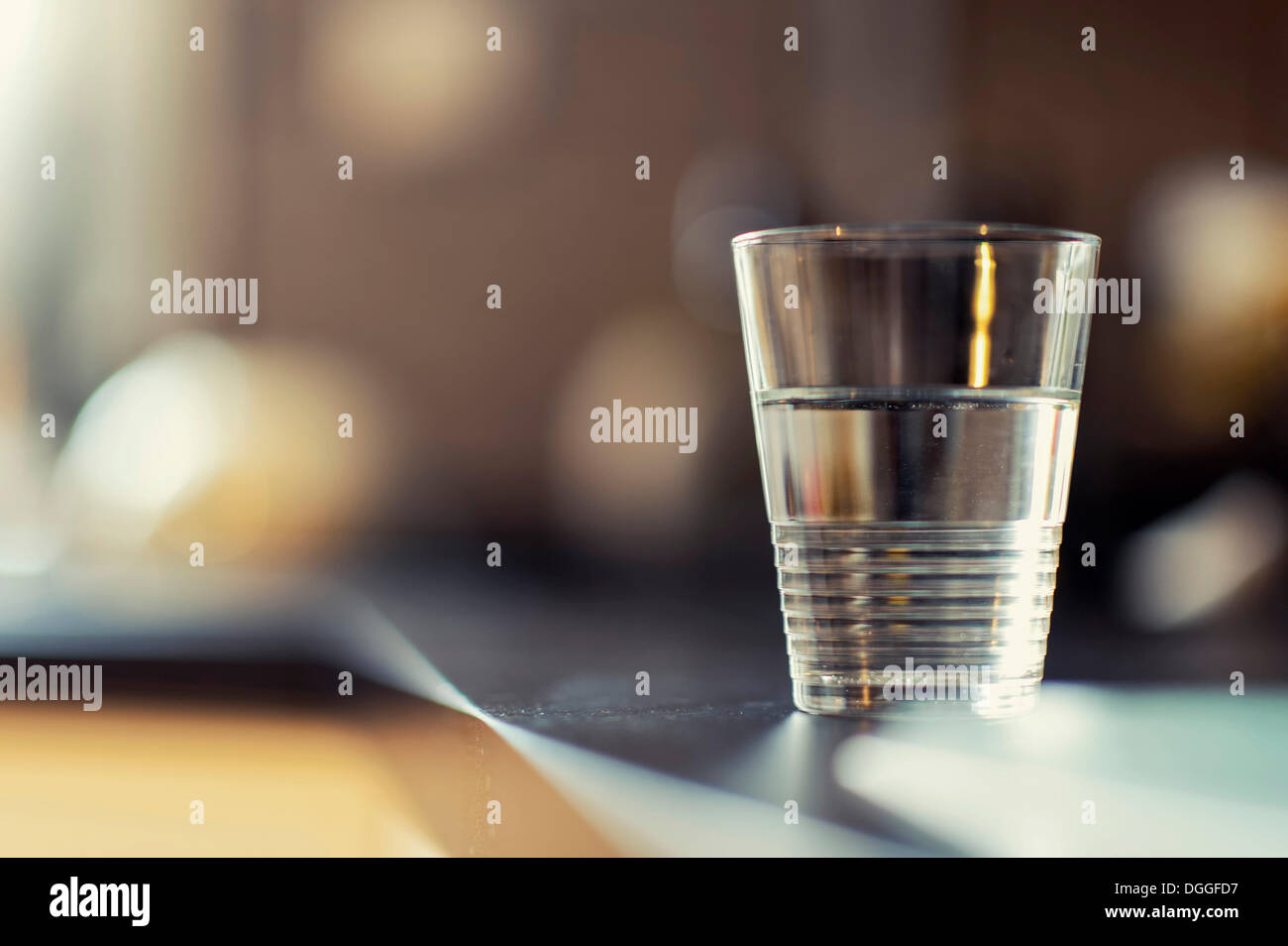 A half-full glass of water standing on a kitchen bench - Stock Image