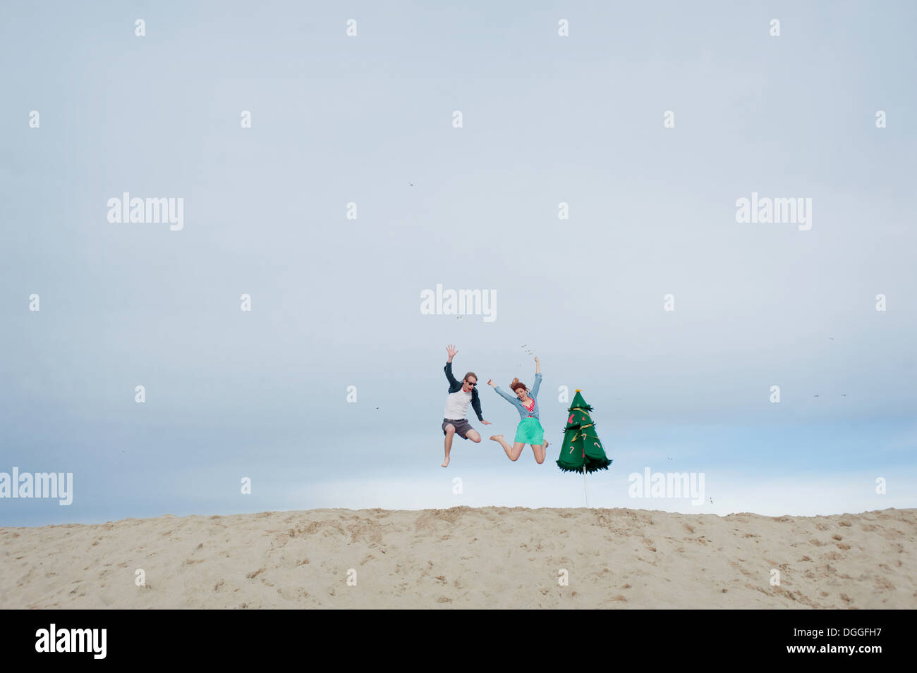 Young couple leaping on beach - Stock Image