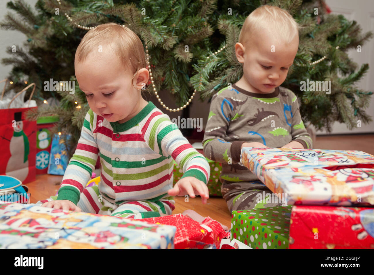Brother and sister looking at Christmas presents - Stock Image