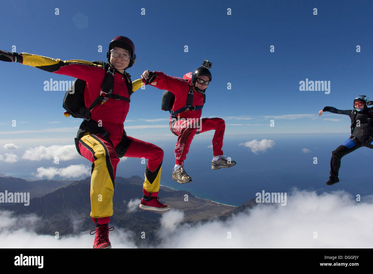 Small group of skydivers reaching to join hands - Stock Image