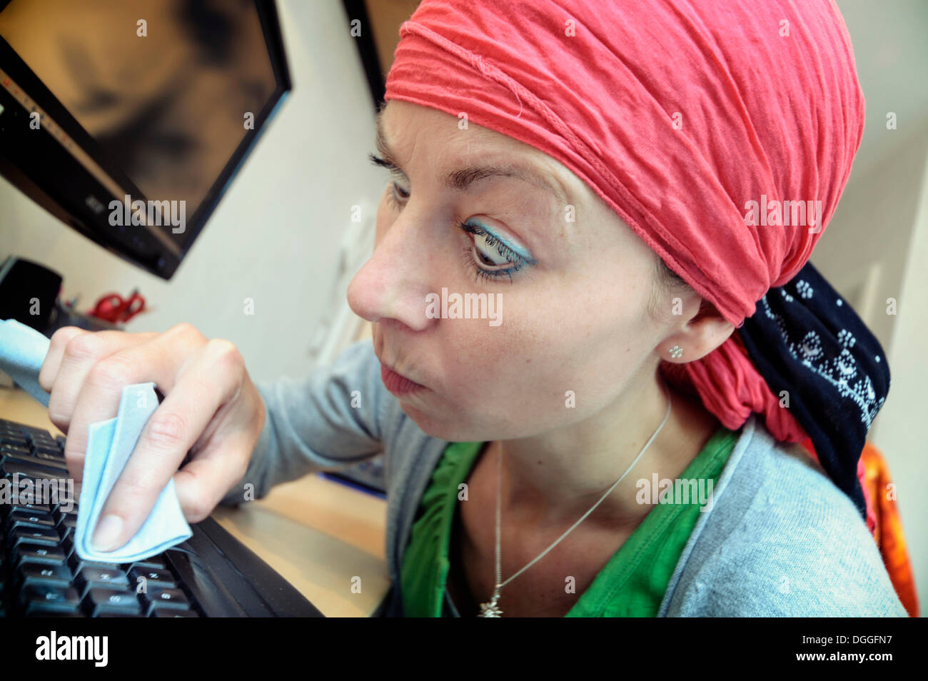 Cleaning lady cleaning a computer keyboard, Germany - Stock Image