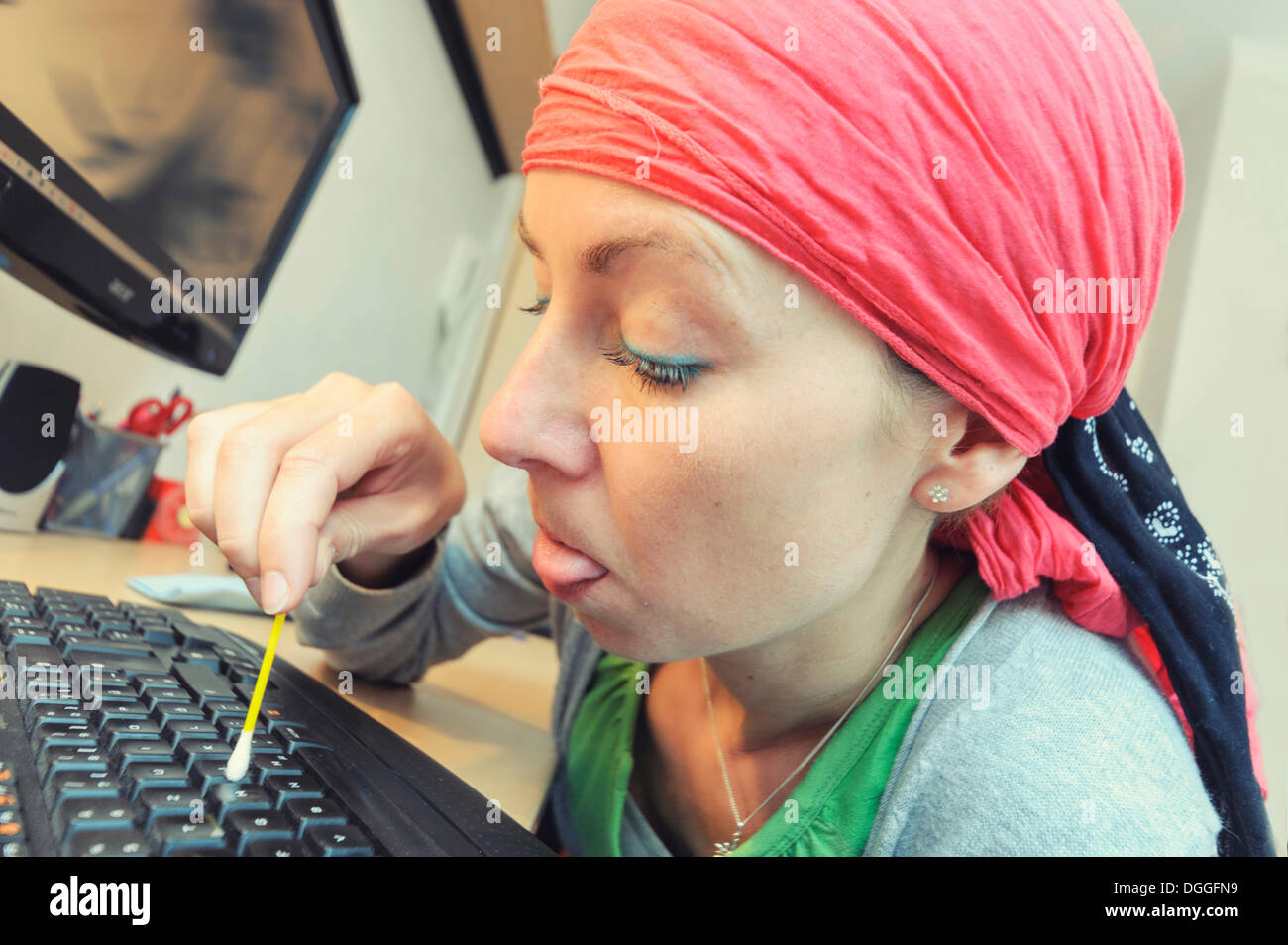 Cleaning lady cleaning a computer keyboard with a cotton swab, Germany - Stock Image