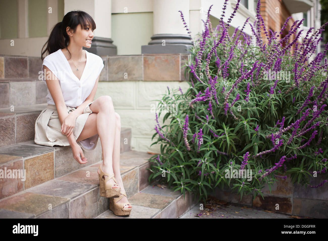 Portrait of young girl sitting on steps at home - Stock Image