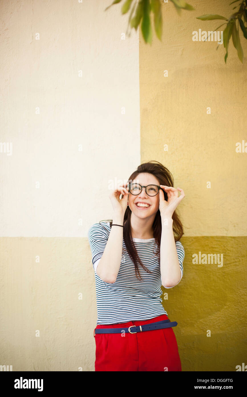 Portrait of young woman in front of color divided wall - Stock Image