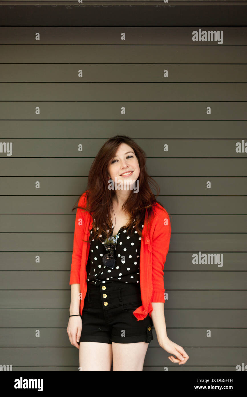 Portrait of young woman in front of shutter - Stock Image