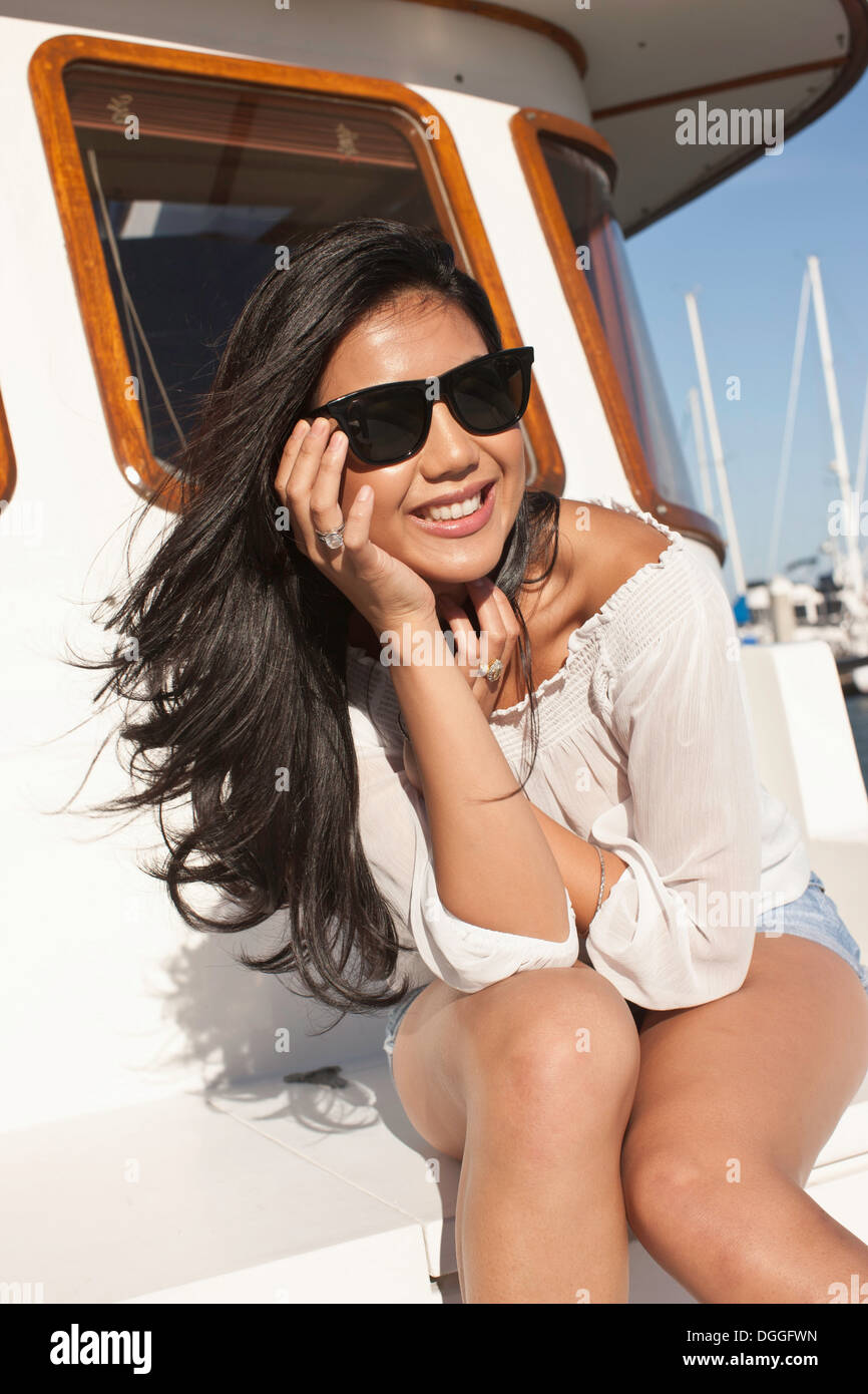 Portrait of young woman sitting on yacht, San Francisco, California, USA - Stock Image