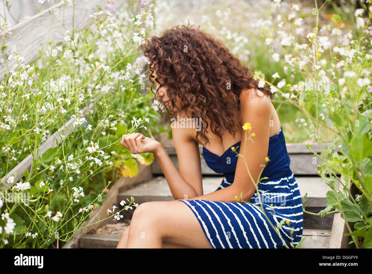 Young woman sitting on wooden steps looking at flower Stock Photo