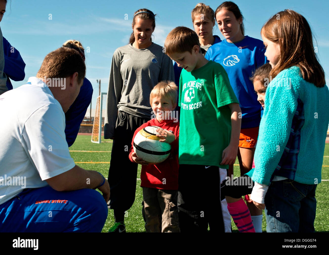 Ed Moore, Boise State University ladies soccer team assistant coach, shows base children how to pass with the inside of their cleats during a soccer clinic for military families at Mountain Home Air Force Base, Idaho, Oct. 5, 2013. The Broncos visited bas - Stock Image