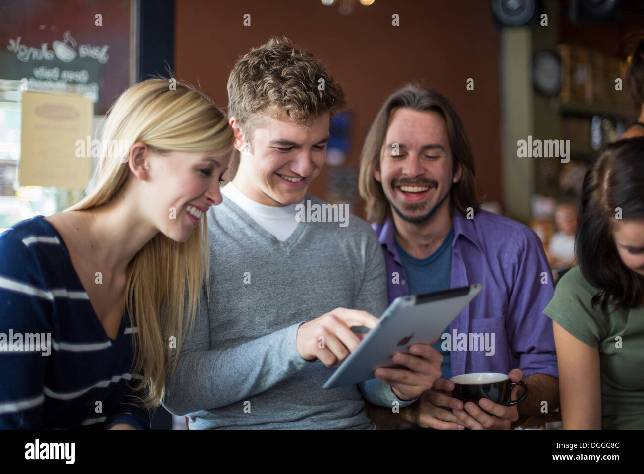 Group of people gathered around digital tablet in cafe - Stock Image
