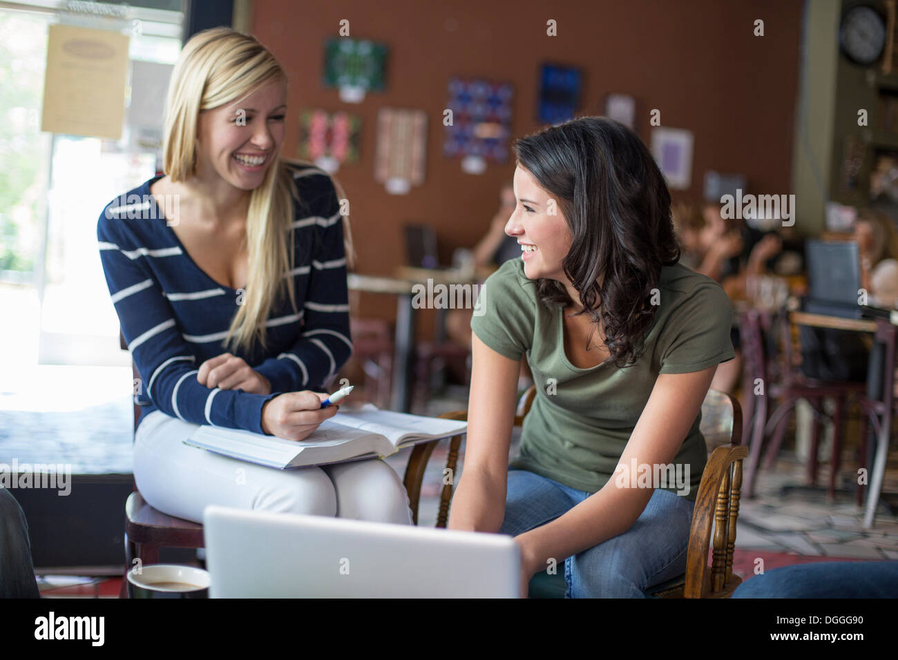 Two teenagers studying with textbooks and computer in cafe - Stock Image