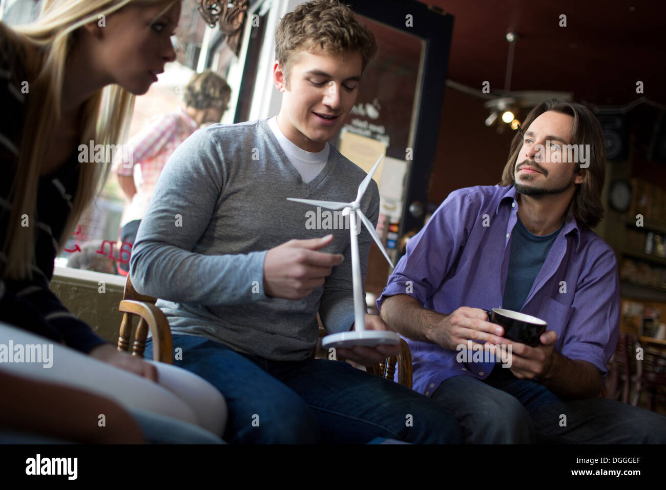 Small study group looking at model in coffee house - Stock Image