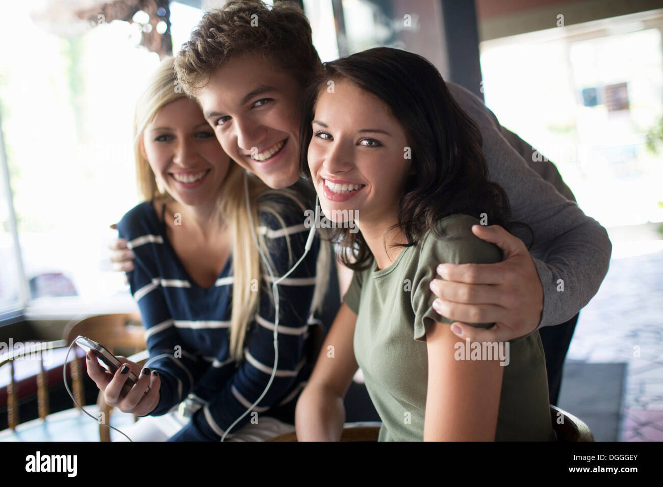 Group of friends sharing earphones in coffee house - Stock Image