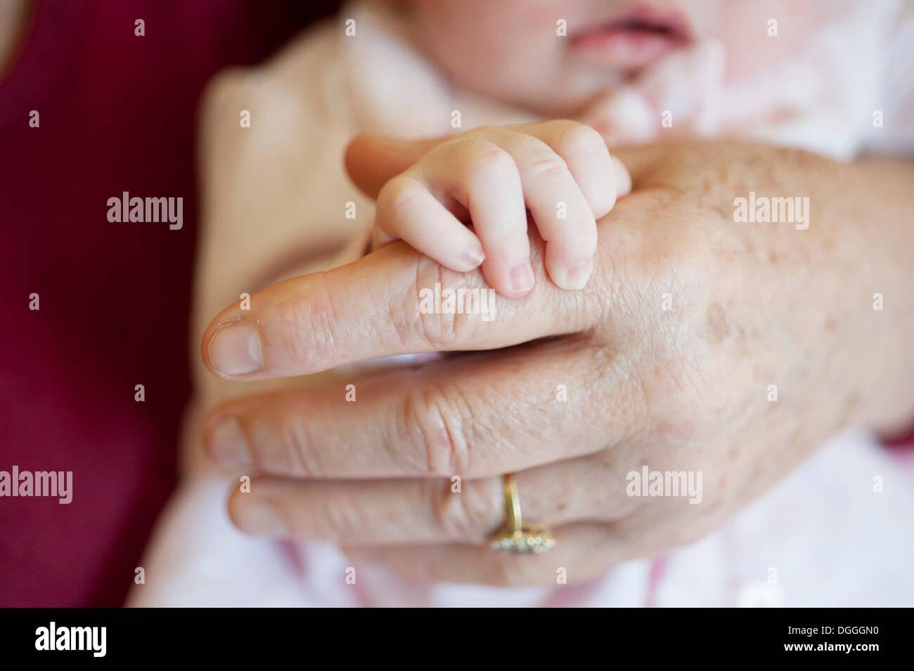 Baby girl holding senior woman's hand, close up Stock Photo