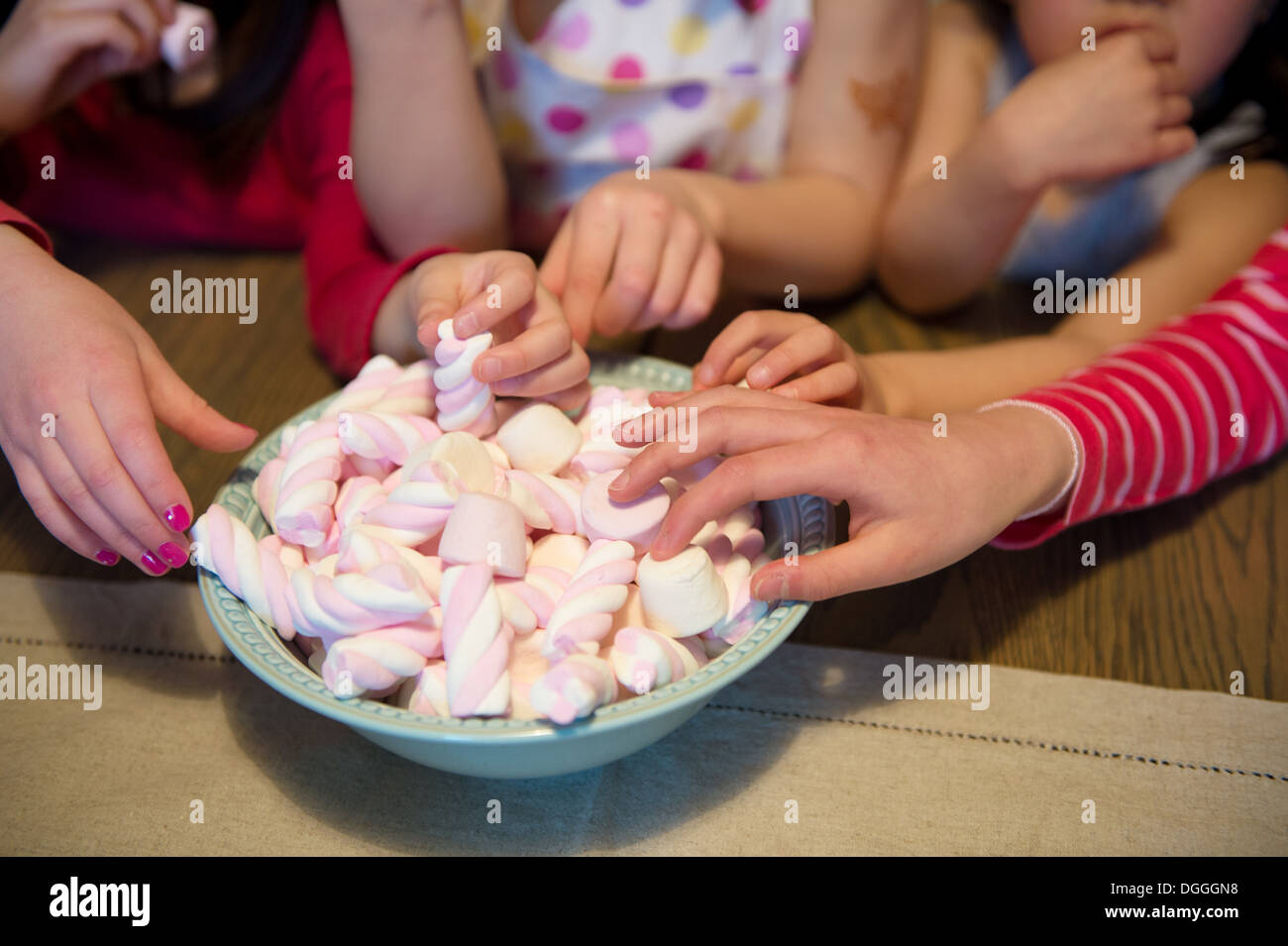 Girls reaching for sweets, close up - Stock Image