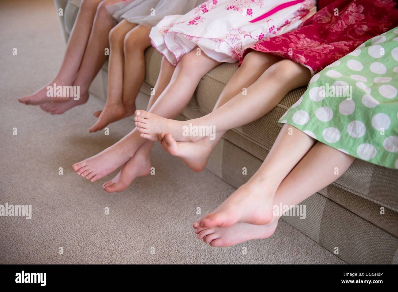 Girls sitting together in a row on sofa - Stock Image