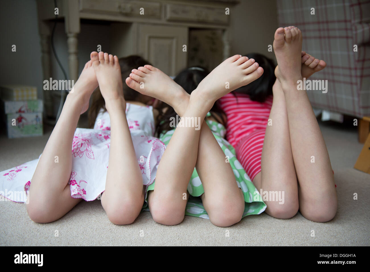 Girls lying on floor together with feet up - Stock Image