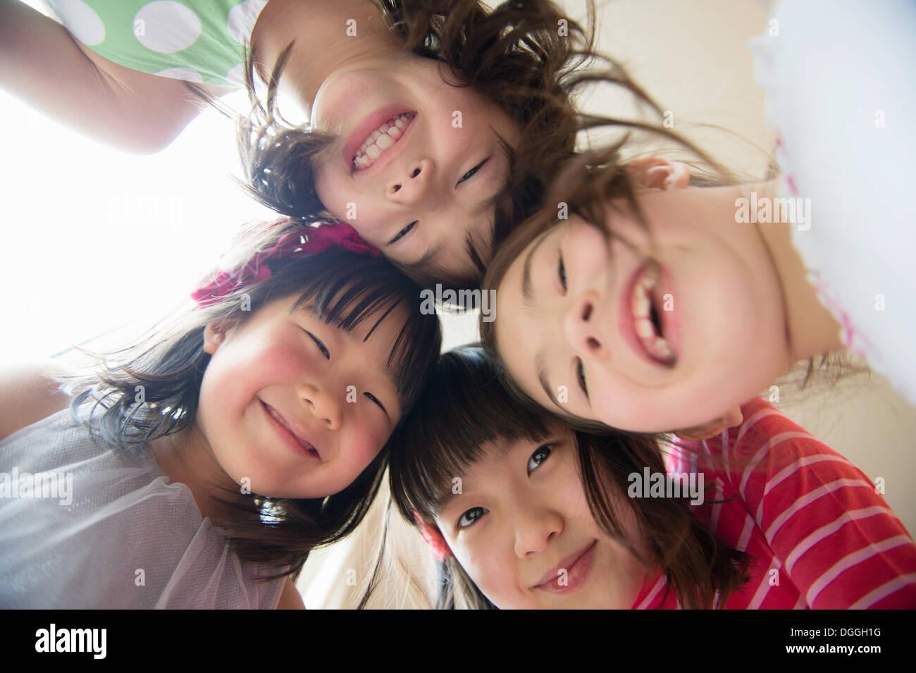 Girls in huddle looking at camera, smiling - Stock Image