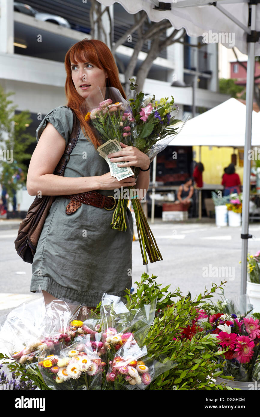 Mid adult woman buying flowers from stall in city - Stock Image