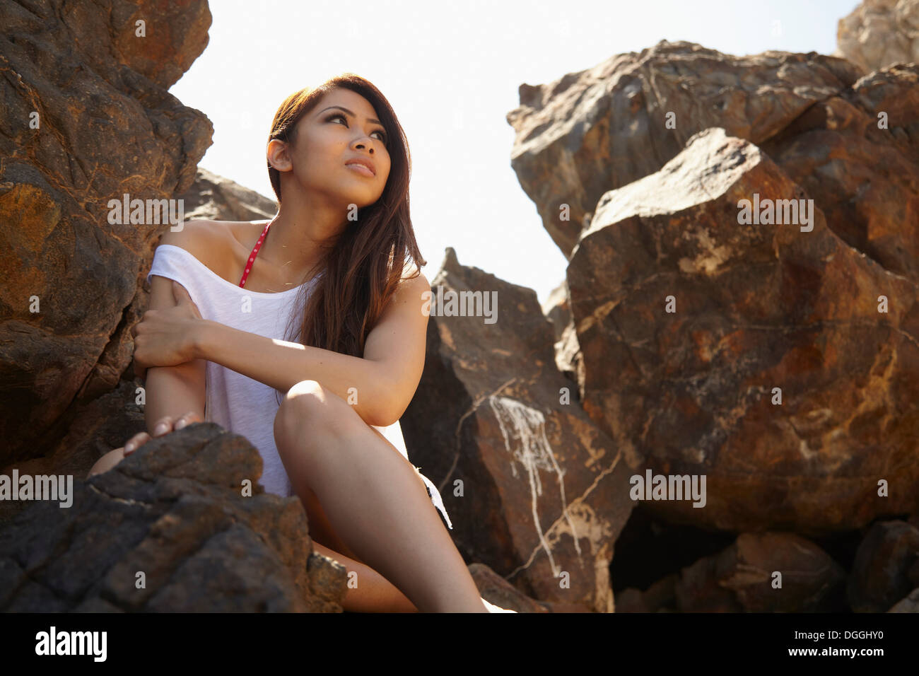 Young woman in rocky shade, Palos Verdes, California, USA - Stock Image