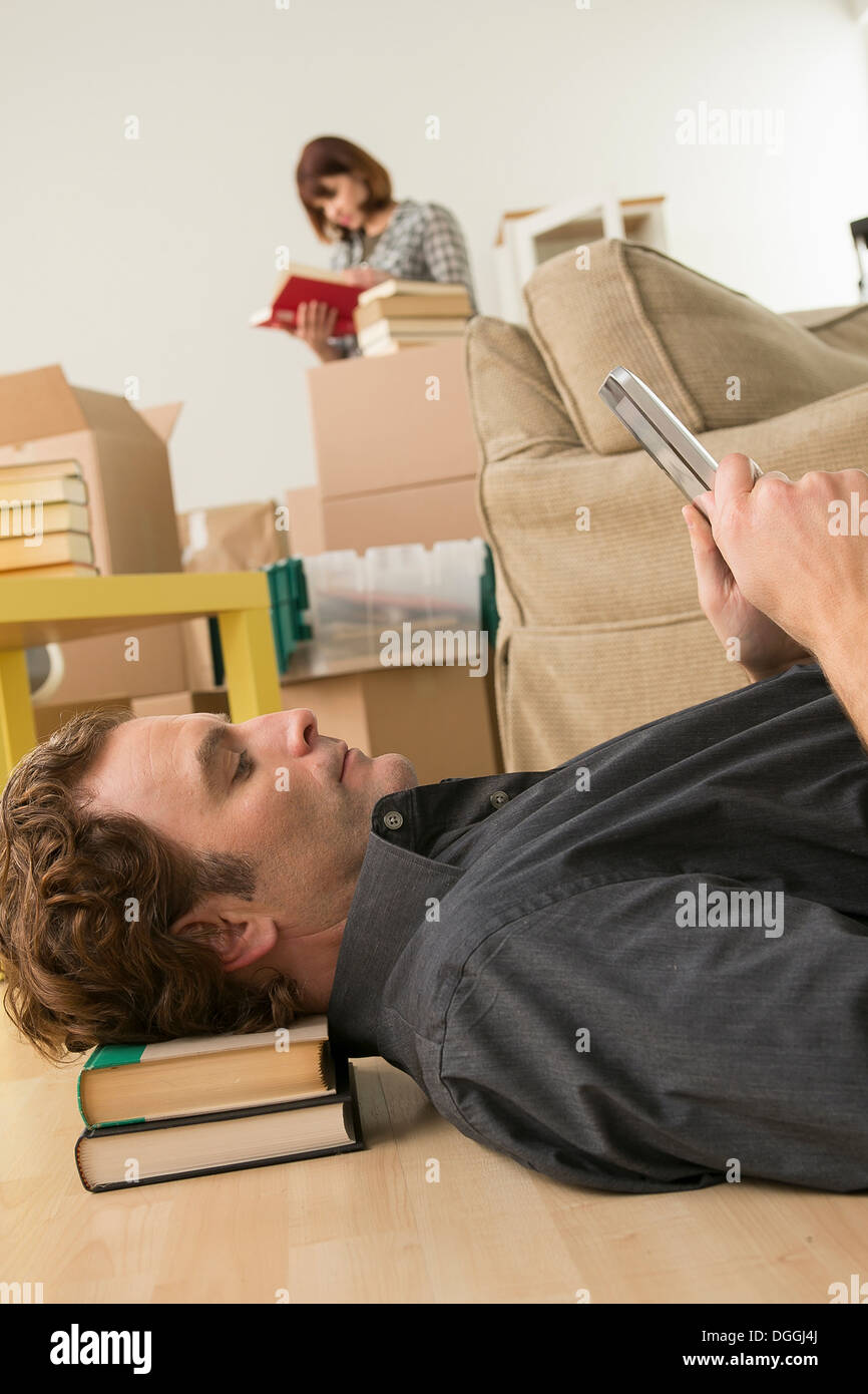 Man lying on floor looking at digital tablet whilst moving - Stock Image