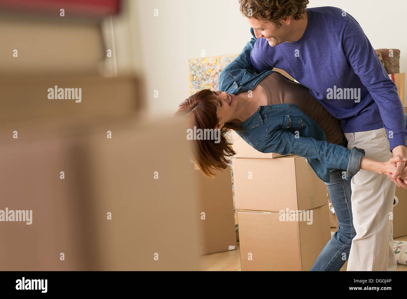 Couple dancing together whilst moving house - Stock Image
