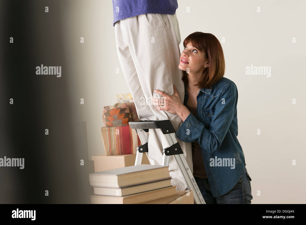 Woman holding onto man on stepladder Stock Photo
