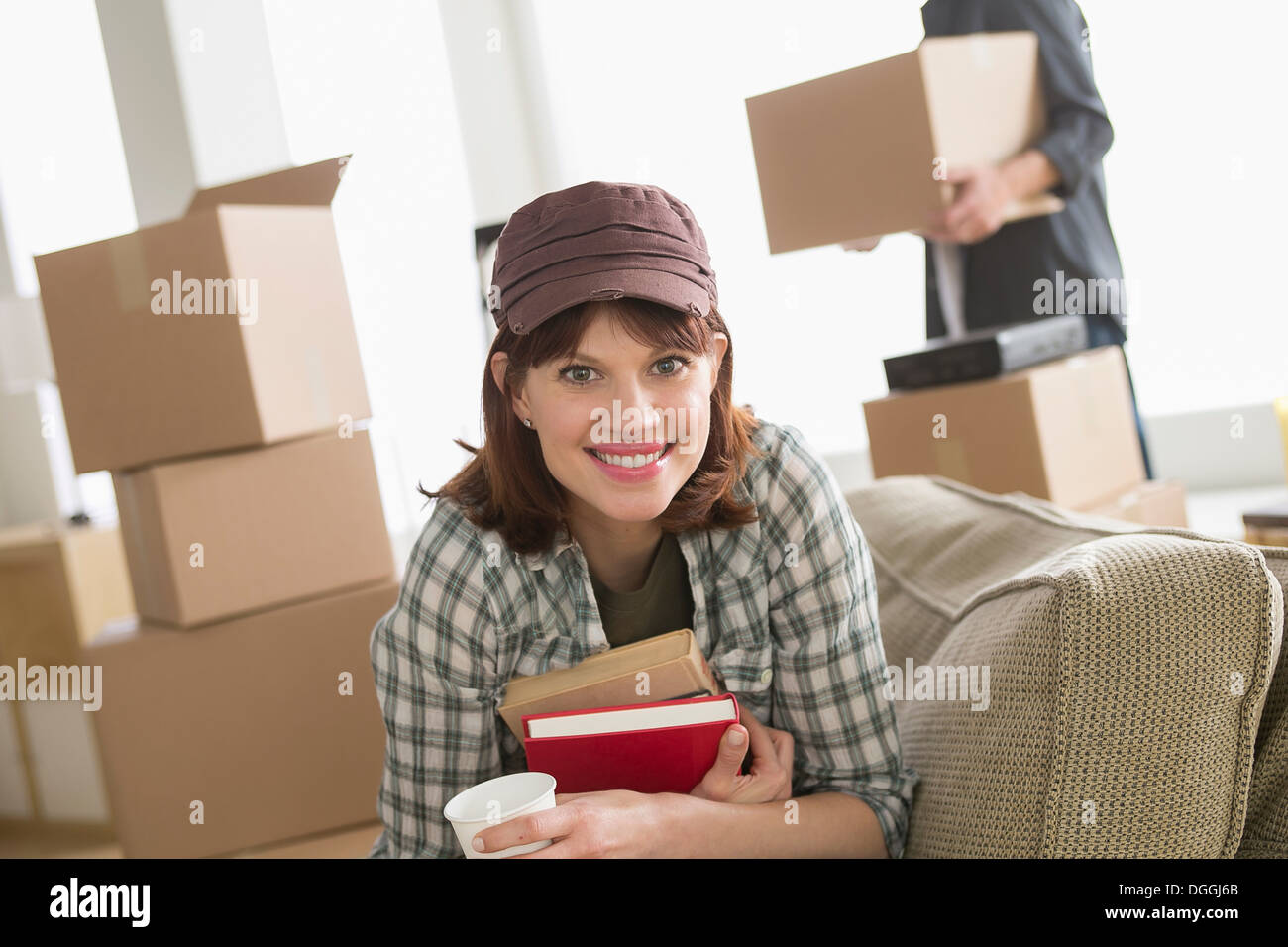 Woman sitting with books whilst moving home - Stock Image
