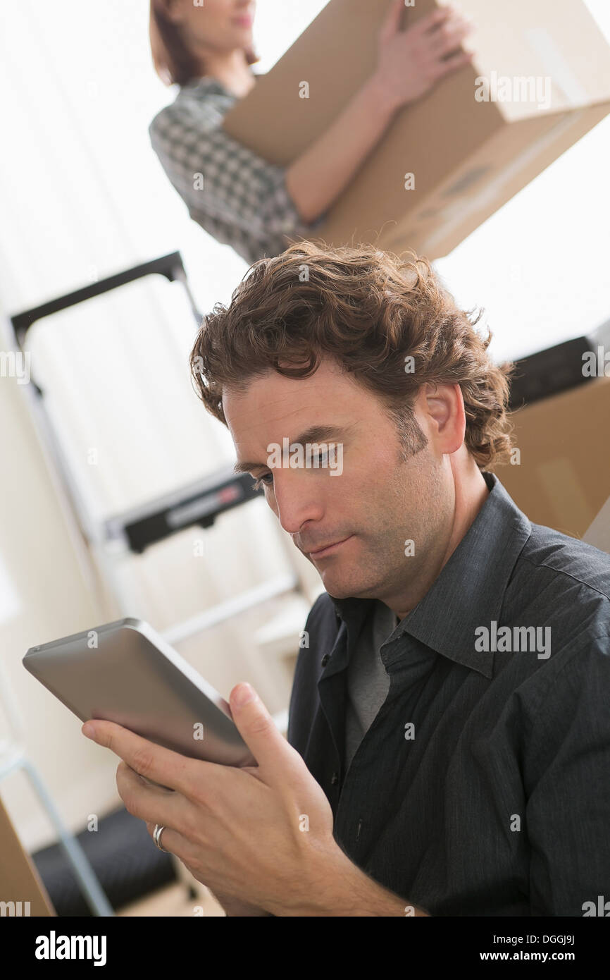 Man looking at digital tablet whilst moving home - Stock Image