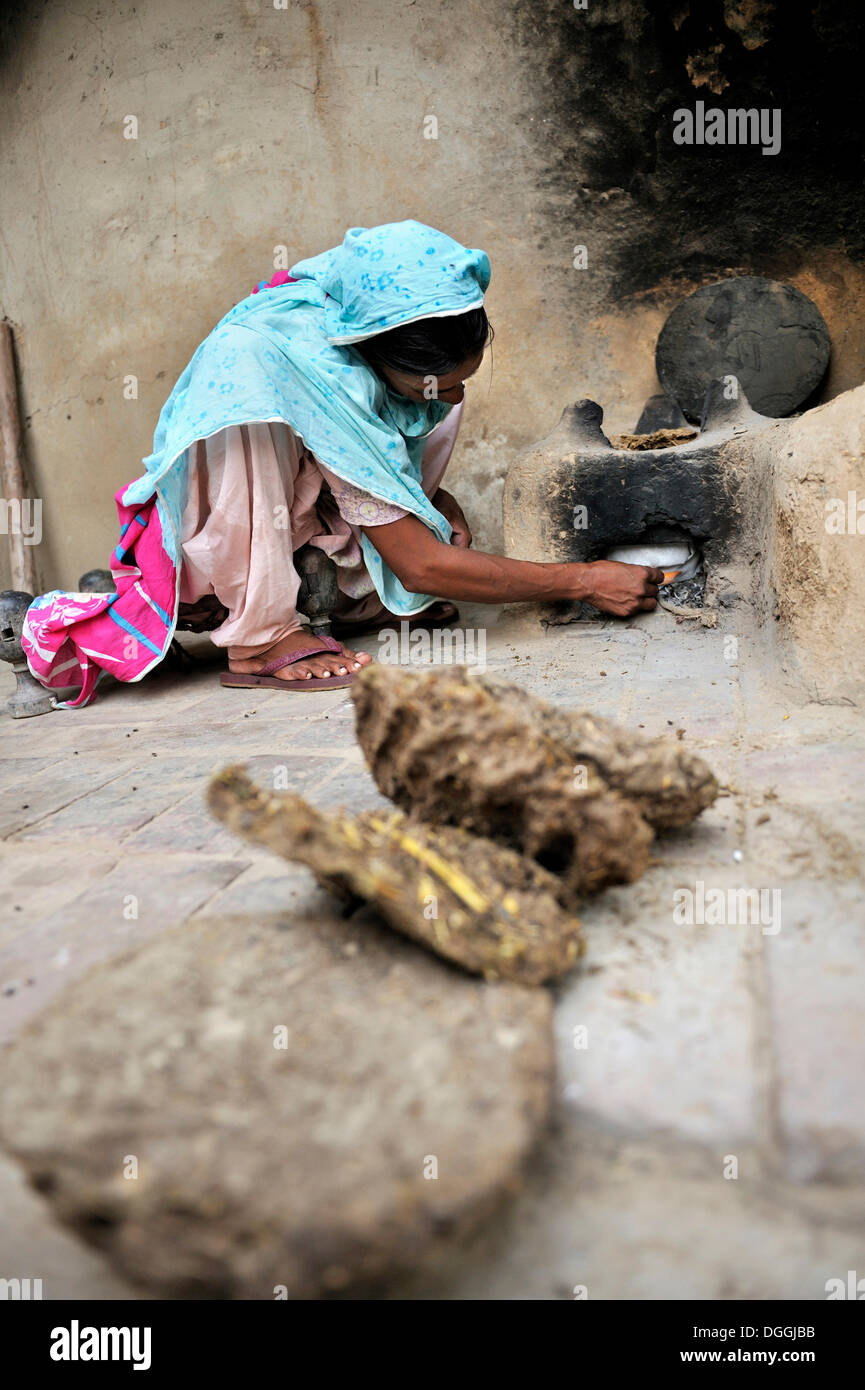 Woman igniting a fire with dried cow dung, she lives and works with her family under the slavery-like practice of debt bondage - Stock Image