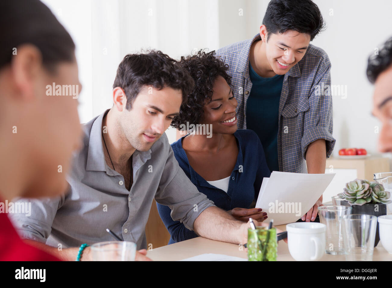 Male and female colleagues meeting in office - Stock Image