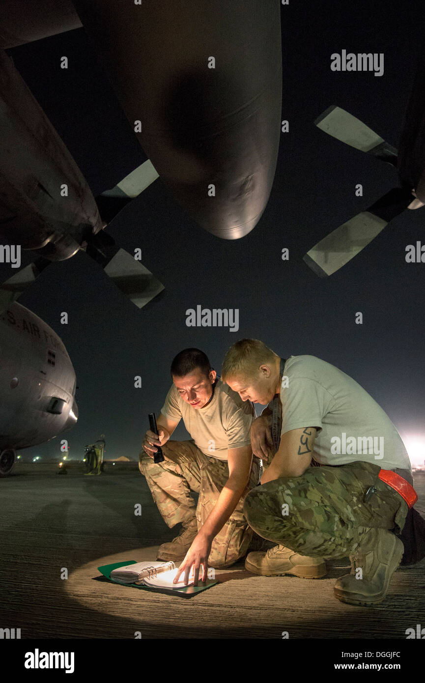 Staff Sgt. Kyle Law and Staff Sgt. Joshua Jorgensen, 774th Expeditionary Airlift Squadron crew chiefs, consult a technical order to troubleshoot a C-130H Hercules engine problem at Bagram Airfield, Parwan Province, Afghanistan, Oct. 6, 2013. Hercules airc - Stock Image